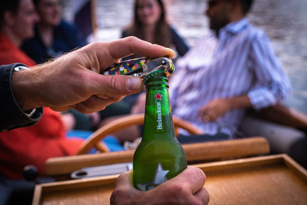 Opening a beer bottle for passengers on a private boat tour in Amsterdam